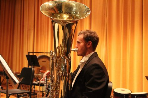 VHS Wind Ensemble Honors tubist senior Kirk Mellring warms up before the concert. Photo by: Lola Bobrow