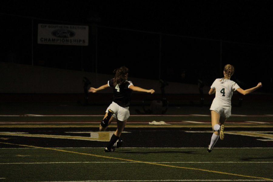 As+Senior+Cassidy+Hubert+%28number+four%29+sprints+down+field%2C+she+attempts+a+mid+range+shot+hoping+to+score+the+Cougars+first+goal.+Photo+By%3A+Gavin+Cross