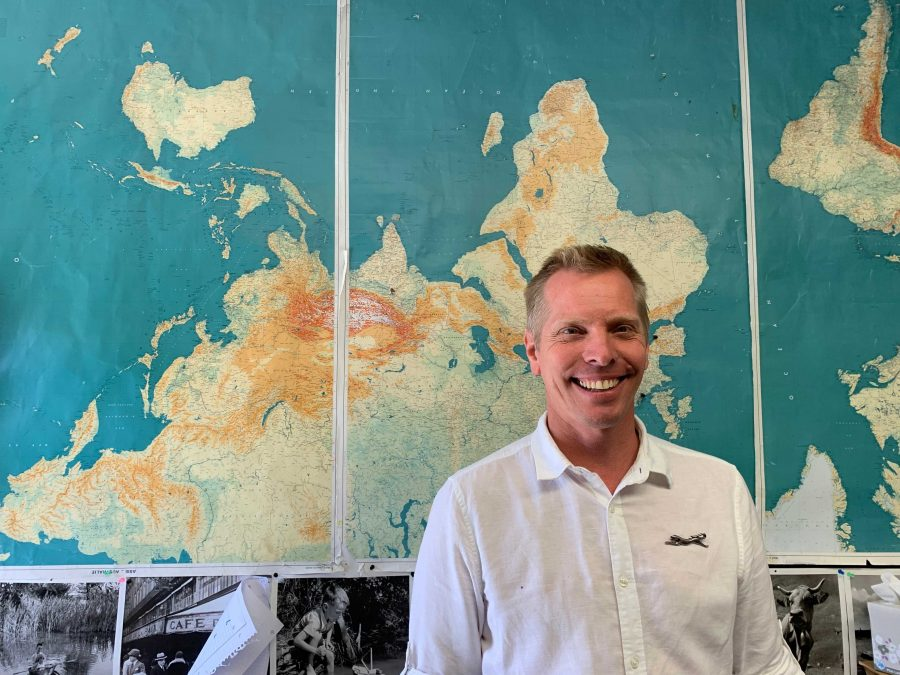 French Teacher, Sebastien DeClerck stands in front of his world map which he uses to educate his students on geography since it is no longer offered at Ventura High School. Photo by: Charlotte D'Orsi