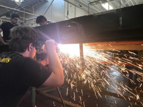 Senior Jefferey Cronin uses a plasma cutter to cut of a piece of steel. Photo by: Kole Petty