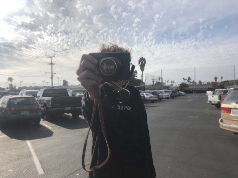 "Hibbler holds the camera that he plans to take the ""unfiltered"" photos on in front of his face to portray that he wants to stay as anonymous as possible. Photo by: Doug Sandford"