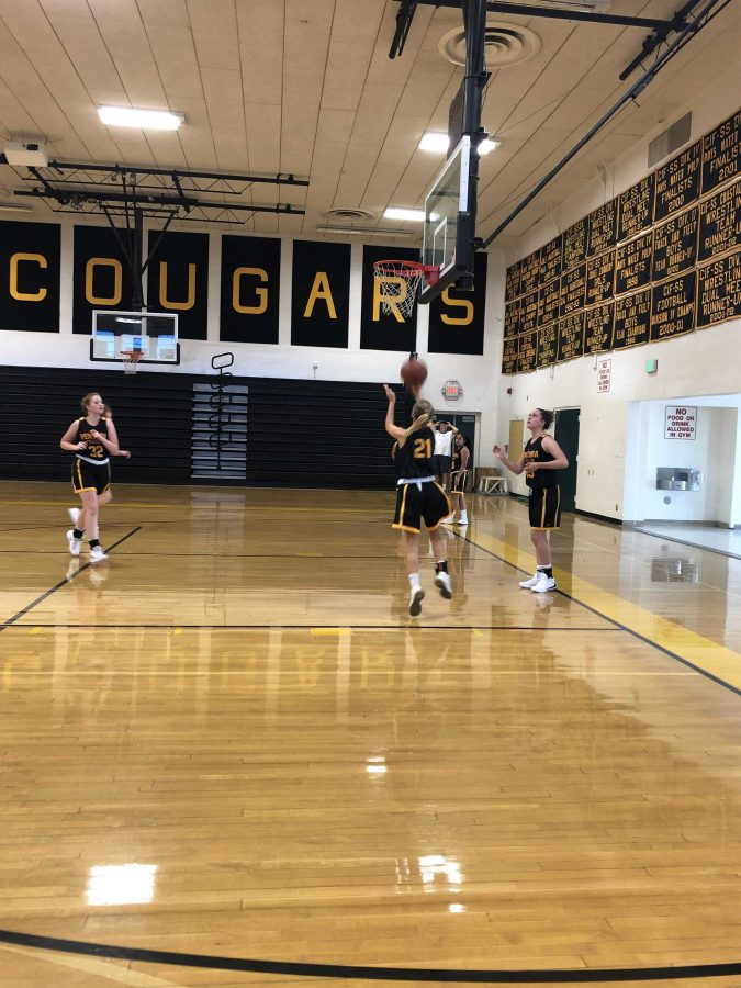 Junior Madeleine Scheer (number 21) went in for a lay up as sophomore Tiernan Philips (number 23, far right) waited to continue the three man weave drill. Photo by Logan Wilkov
