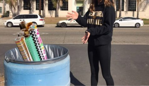 "Sophomore Izzy Eulenhoefer says she is ""so surprised that there is so much waste during the holidays"" as she gestures to a trash can with photoshopped wrapping paper. - photo by Audrey Flynn"