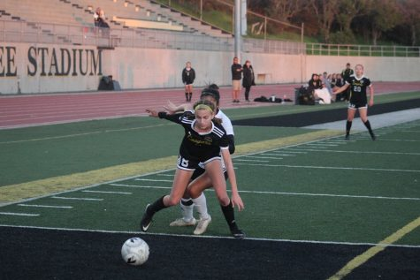 Freshman Maddy Dannenberg (number 8) fights for the ball against Rio Mesa. Photo by: Jocelyn Lee